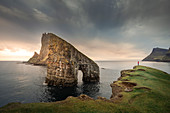 Person in sunset in front of Drangarnier rock formations on Vagar, Faroe Islands