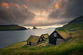 Houses with grass roofs in sunset in front of Drangarnier rock formations on Vagar, Faroe Islands