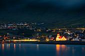 Beleuchtete Kirche bei Nacht im Dorf von Sandavágur auf der Insel Vagar, Färöer Inseln\n