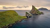 Felsformationen von Drangarnier und Insel Tindholmur und Mykines im Sonnenuntergang auf Vagar, Färöer Inseln