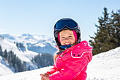 Child in the snow in St. Johann in Tirol with Kitzbühel Alps in the background, St. Johann, Tyrol, Austria