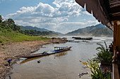 Longtail boats on the Mekong River seen from the Mekong Sun river cruise ship, Pak Tha District, Bokeo Province, Laos, Asia