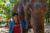 A mahout stands next to an elephant in an elephant reception center, Pak Ou, Luang Prabang Province, Laos, Asia