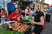 Young blonde woman laughs together with a saleswoman selling coconut pancakes at a stall along Sisavangvong Road (the main street), Luang Prabang, Luang Prabang Province, Laos, Asia