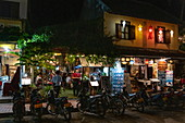 Mopeds stand outside busy restaurant and bar on Sisavangvong Road (the main street), Luang Prabang, Luang Prabang Province, Laos, Asia