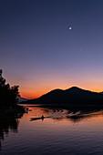 Silhouette von Longtail-Boot auf Fluss Mekong und Berge bei Sonnenuntergang mit Mondsichel und Venus, Luang Prabang, Provinz Luang Prabang, Laos, Asien