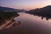 Aerial view of river cruise ship Mekong Sun moored on the sandy bank of the Mekong River at dusk, Ban Hoy Palam, Pak Tha District, Bokeo Province, Laos, Asia