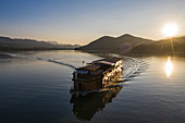 Aerial view of river cruise ship Mekong Sun  on river Mekong with mountains behind at sunset, Chomphet District, Luang Prabang Province, Laos, Asia