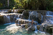 Aerial view of a beautiful young blonde woman on a rock in the natural pools of the magnificent Kuang Si Falls, Kuang Si, Luang Prabang Province, Laos, Asia