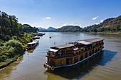 Aerial view of river cruise ship Mekong Sun  and local excursion boats on the banks of the Mekong River, Luang Prabang, Luang Prabang Province, Laos, Asia