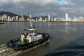 Tugboat with city skyline behind, Itajai, Santa Catarina, Brazil, South America