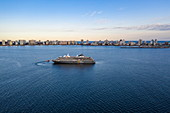 Aerial view of expedition cruise ship World Explorer (Nicko Cruises) with city skyline behind at sunset, Punta del Este, Maldonado Department, Uruguay, South America
