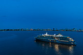 Aerial view of expedition cruise ship World Explorer (Nicko Cruises) with city skyline behind at dusk, Punta del Este, Maldonado Department, Uruguay, South America