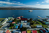 Aerial view of city center with expedition cruise ship World Explorer (Nicko Cruises) behind it, Stanley, Falkland Islands, British Overseas Territory, South America