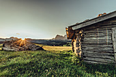 destroyed hut at sunrise on the Seiser Alm in South Tyrol, Italy, Europe;