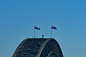 The Harbor Bridge with Australia flags against a blue sky, Sydney, New South Wales, Australia
