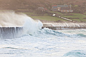 Waves crash on the harbor wall of Goury in a storm, Cotentin, Normandy, France