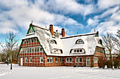 Snow-covered thatched roof house, Dorum, Lower Saxony, Germany