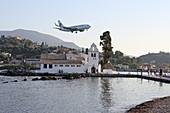 Landing plane over the Vlacherna Monastery in the Kanoni district, Kerkira, Corfu Town, Analipsi Peninsula, Corfu Island, Ionian Islands, Greece