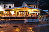 Taverna Nikolas in the small Agni Bay on the northeast coast of the island of Corfu is a popular restaurant with its own boat taxi that brings guests from the adjacent bays, Ionian Islands, Greece