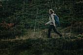 Woman wanders through rain, mountain, Switzerland,