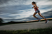 Woman runner runs on road in sunset, sport, forest