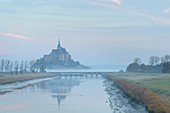 France, Manche, the Mont-Saint-Michel, view of the island and the abbey at sunrise from the mouth of the Couesnon river