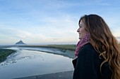France, Manche, the Mont-Saint-Michel, young woman look the island and the abbey at sunrise from the mouth of the Couesnon river