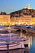 France, Bouches du Rhone, Marseille, Vieux Port and its sharp (traditional fishing boats) with at the bottom the Basilica of Our Lady of the Guard