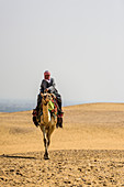 Man riding a camel in the desert outside Cairo