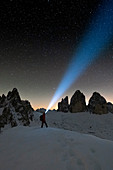 Hiker with head torch admiring stars on Monte Paterno and Tre Cime di Lavaredo, Sesto Dolomites, South Tyrol, Italy, Europe