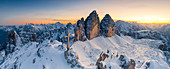 Summit cross on snow capped Monte Paterno with Tre Cime Di Lavaredo in background at sunset, Sesto Dolomites, South Tyrol, Italy, Europe