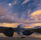Matterhorn peak lit by moon in the starry night sky viewed from Stellisee, Zermatt, Valais canton, Switzerland, Europe