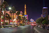 View along The Strip by night, illuminated Eiffel Tower at the Paris Hotel and Casino prominent, Las Vegas, Nevada, United States of America, North America