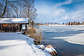 Boathouse on the shore of the frozen Lake Bayersoien, Bad Bayersoien, Upper Bavaria, Bavaria, Germany