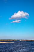White cloud in blue sky with river cruise ship on Volga river in the distance, near Nizhny Novgorod, Nizhny Novgorod District, Russia, Europe