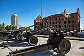 Artillery on display in front of the Gerhardt Mill (one of the few remaining buildings from the Battle of Stalingrad in World War II), Volgograd, Volgograd District, Russia, Europe