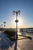 Silhouette of street lamps and people walking along promenade on the bank of Volga river, Astrakhan, Astrakhan District, Russia, Europe