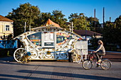 Woman on bicycle in front of snack bar in the design of a carriage along promenade on the bank of Volga River, Astrakhan, Astrakhan District, Russia, Europe