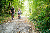 Portrait of smiling mature couple riding bicycles on footpath in forest