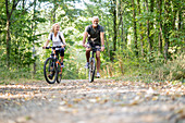 Smiling mature couple riding bicycles in forest