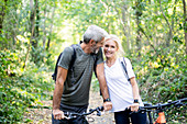 Smiling mature couple with bicycles standing in forest