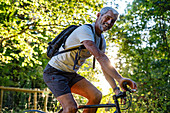 Portrait of smiling mature man cycling in forest