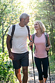 Smiling mature couple looking at each other while hiking in forest