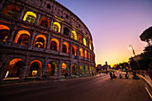 Low angle view of tourists walking on street outside Colosseum at dusk,Rome