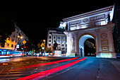 Macedonia Gate with light trail of traffic driving on street in foreground,Skopje city