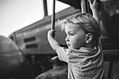 Boy climbs on a tractor, black and white