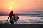 Female surfer goes with surfboard on the beach in sunset, surfing, Portugal, sunset