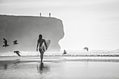 Female surfer walks on the beach in Portugal with her surfboard, surfing, Portugal