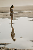 pregnant woman is standing on the beach in the evening light
